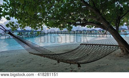 On The Sandy Beach, Under The Shade Of A Tree, There Is A Net Hammock. Above The Tranquil Aquamarine