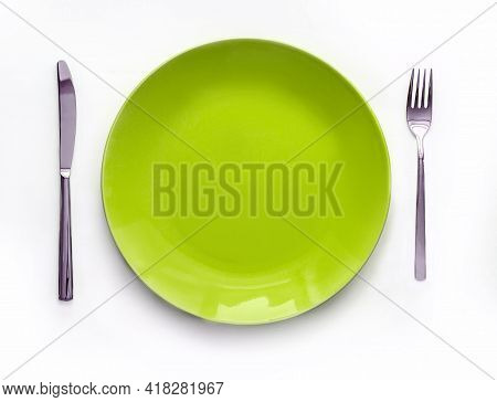 Served Plate With Cutlery. Empty Green Plate And Stainless Knife And Fork Isolated On White Backgrou