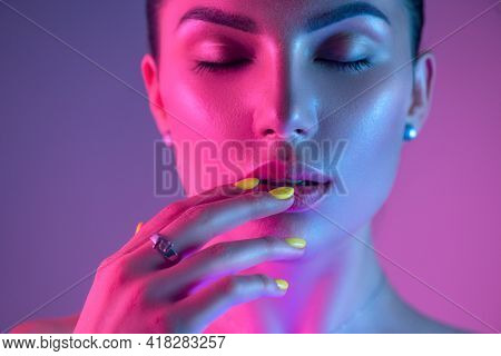 High Fashion model girl in colorful bright UV lights posing in studio, portrait of beautiful woman with trendy make-up and manicure. Art design, colorful make up. Over colourful purple background.