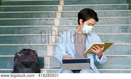 Young Asian Campus Student Man Wearing Protection Mask While Online Study In Campus By Digital Table