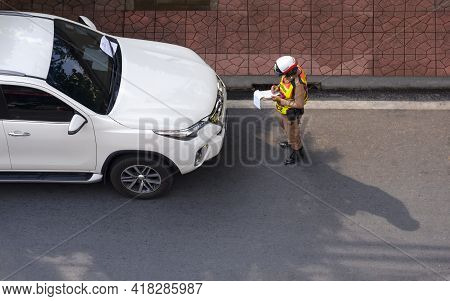 Bangkok, Thailand - April 12,2021: Top View Of Asian Policeman Writing Traffic Ticket For White Car