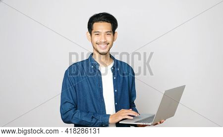 Young Asian Man Holding Laptop Computer Smiling And Looking At Camera Standing On Isolated Grey Back