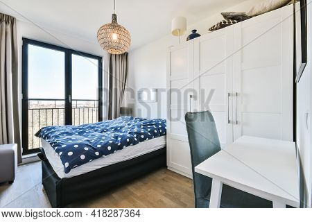 Comfortable Bed With Spotted Duvet Located Near Wardrobe And Table With Chair In Minimalist Style Be