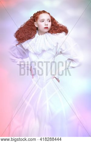 Sophisticated female model with lush curly hair posing in a white art dress with collar. A studio portrait with mixed color lighting in haze. Fashion art.