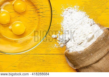 A Bag Of Flour And Broken Chicken Eggs In A Glass Bowl. Ingredients For The Dough. Products For Doug