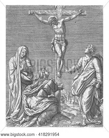 Christ on the cross. On the left, Mary Magdalene is kneeling with both hands, embracing the cross, and to her left, Mary is standing with her hands together.