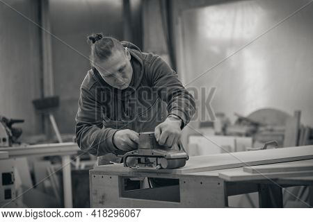 Close Up. Carpenter At Workshop Polishes Wooden Board With A Electric Orbital Sander. Woodwork And F