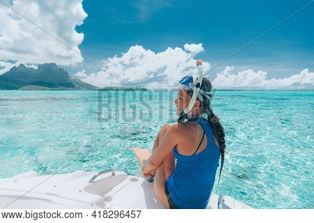 Snorkeling from boat in Bora Bora, Tahiti, French Polynesia. Woman jumping in crystal clear water with snorkel gear in coral reef lagoon with Bora Bora landmark Mount Otemanu in background.