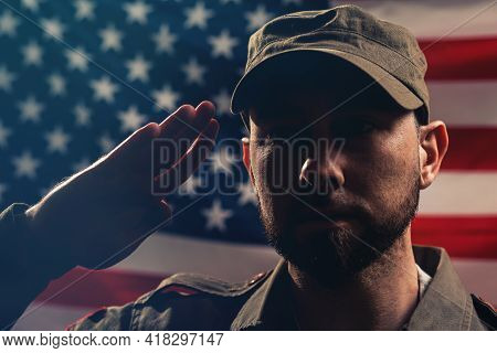 Memorial Day. A Portrait Of Uniformed Soldier Salutes Against The Background Of The American Flag. C
