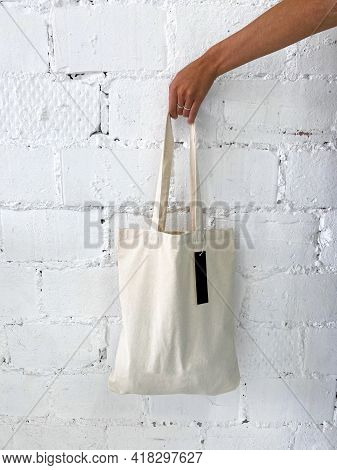 Womans Hand Holding A New White Tote Bag Or Shopper With Blank Label