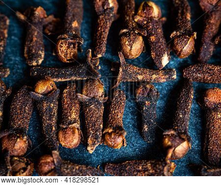 Close-up Of Cloves On A Dark Blue Background Shot Overhead