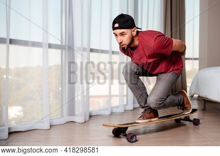 A Young Man In Casual Clothes Poses On A Longboard, Imagining That He Is Driving Down The Street. In