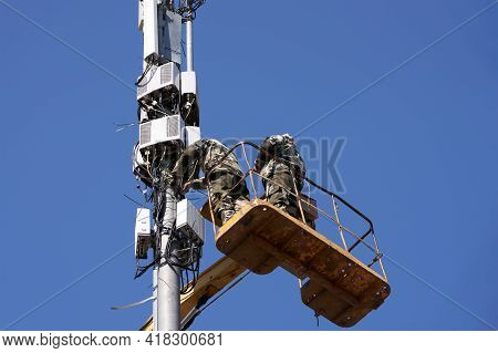 Installation Of Cellular Equipment On The Tower. Two Communications Engineers Work At Altitude From