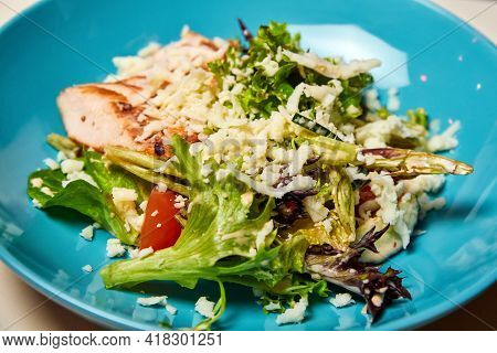Blue Bowl Of Caesar Salad With Chicken Sous-vide.