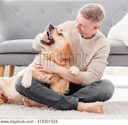 Man playing with golden retriever dog and petting him sitting on the floor. Doggy shows teeth