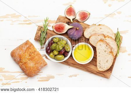 Ripe olives, olive oil, figs and ciabatta bread. Top view flat lay