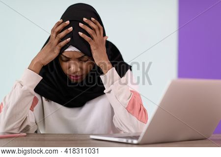 afro girl wearing a hijab is disappointed and sad sitting in her home office and using a laptop
