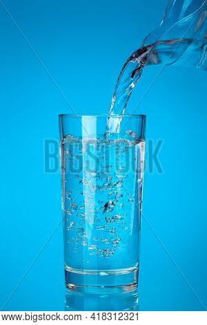 Glass Cup Filled With A Stream Of Fresh Drinking Water From A Jug Spout With Bubbles And Splashes, D