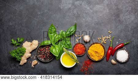 Various spices, herbs and condiments on dark stone table. Indian cuisine. Top view flat lay with copy space