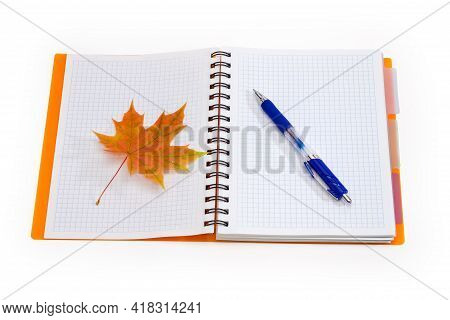 Open School Exercise Book With Spiral Binding And Sheets Of Blank Squared Paper, Pen And Autumn Leaf