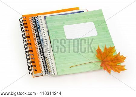 Different Closed School Exercise Books With Ordinary And Spiral Binding And Autumn Leaf On Them On A