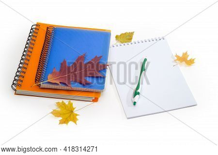 Two Closed Paper Notebooks With Spiral Binding, Open Notepad With Pen And A Few Autumn Leaves On A W
