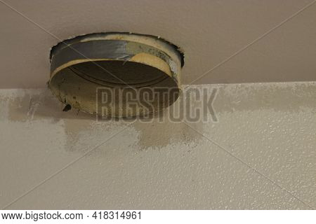 Dismantled Vent Hood Petruding From A Kitchen Ceiling