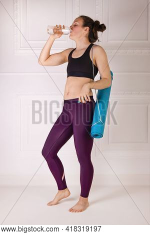 Attractive Young Woman With Blue Yoga Or Fitness Mat Drinks Water After Working Out. Strength And Mo