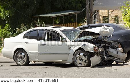 Road Accident. Collision Of Cars At High Speed. Wrecked White Car