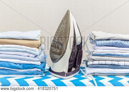 Electric Iron On The Ironing Board And A Pile Of Colorful Clothes Stacked On The Ironing Board