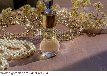 Oil Perfume In Beautiful Bottle With White Pearls Necklace And Accessory On Toilette Table. Selectiv