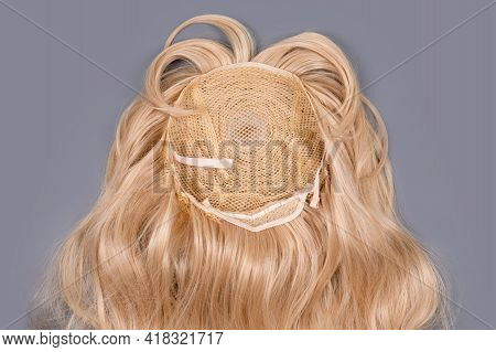 Female Blonde Wig Close Up On Grey Background. Golden Human Hair Weaves, Extensions And Wigs. Woman