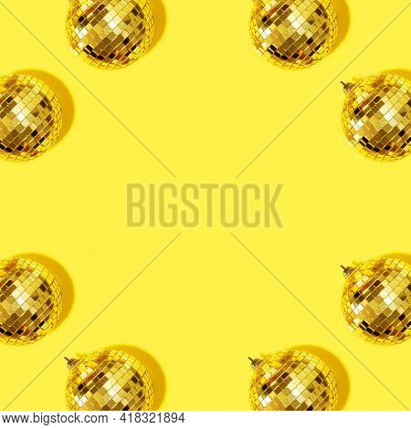 Frame With New Year Baubles. Shiny Gold Disco Balls On Yellow Background. Pop Disco Style Attributes