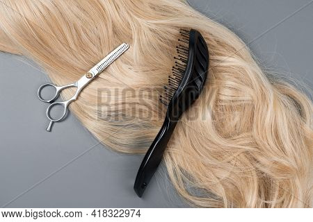Hairdresser Professional Thinning Scissors Or Shears And Hairbrush With Blonde Hair On Grey Backgrou
