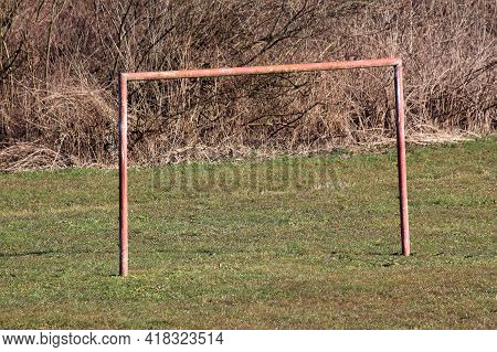 Rusted Old Metal Goal Post Without White Net Used For Soccer Practice At Local Public Park Surrounde