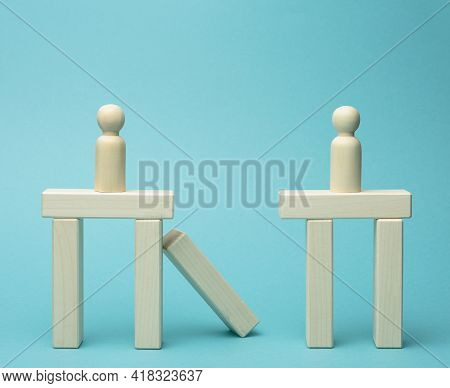 Little Wooden Men Stand On The Destroyed Bridge On Different Sides On A Blue Background. The Concept