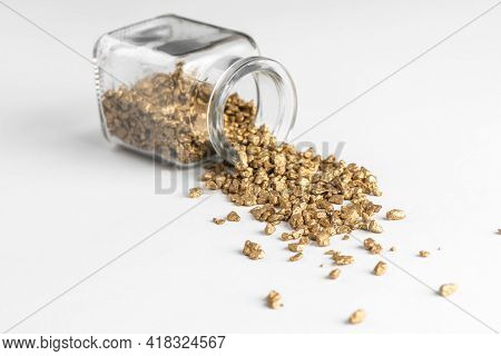 Laying Glass Bottle With Spilled Golden Nuggets On White Background