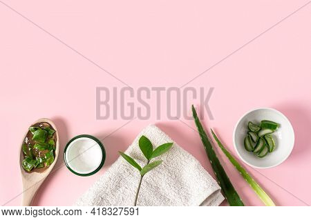 Top View Of Wooden Spoon With Aloe Vera Juice, Organic Cream, Gel, Towel And Green Leaves. Flat Lay