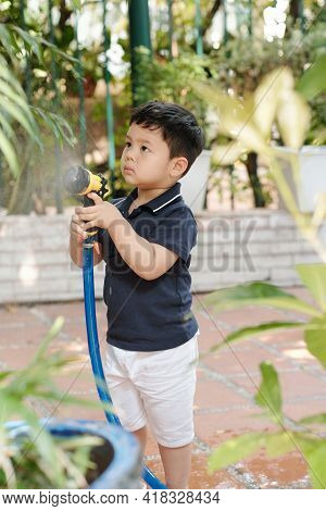 Concentrated Serious Little Mixed-race Boy Watering Plants And Trees In Backyard