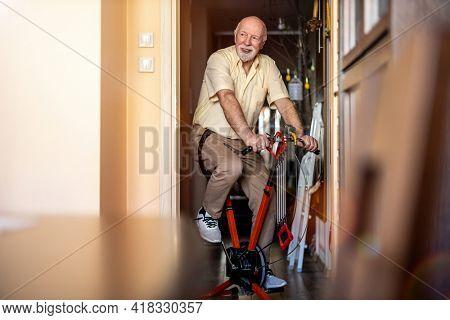 Senior man using exercise bike at home