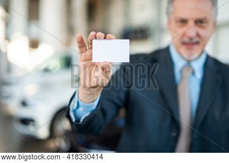 Car dealer showing his business card