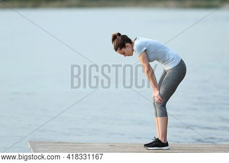 Side View Portrait Of A Fatigued Runner Stopping And Resting After Sport In A Lake Pier
