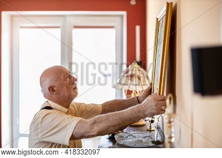 Senior man putting up a painting on the wall at his home
