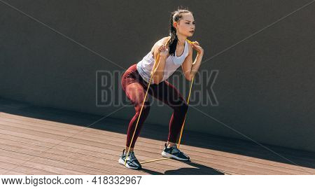 Full-length View Of An Athlete Female Working With The Elastic Band Outside On Grey Background. Heal