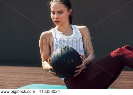 Horizontal Sporty Young Woman Doing Exercises With A Medicine Ball Outdoors On A Sunny Day. Fitness
