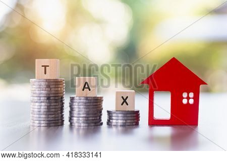 Taxes. Investments In Real Estate. Graph Of The Growth Of A Pile Of Silver Coins And A Red Wooden Ho