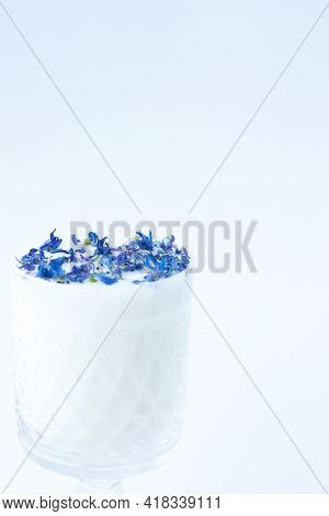 Beautiful Crystal Glass With Milk And Blue Flower Petals On A White Background. Abstract Background.