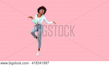 Bushy Black Woman Jumping Posing In Mid-air, Pink Background, Panorama