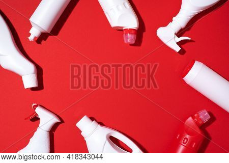 Composition With Plastic Bottles Of Cleaning Products Over Red Background. Top View. Flat Lay. Copy