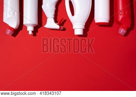 Detergent Bottles And Chemical Cleaning Supplies On Red Background. Top View. Copy Space. Flat Lay.